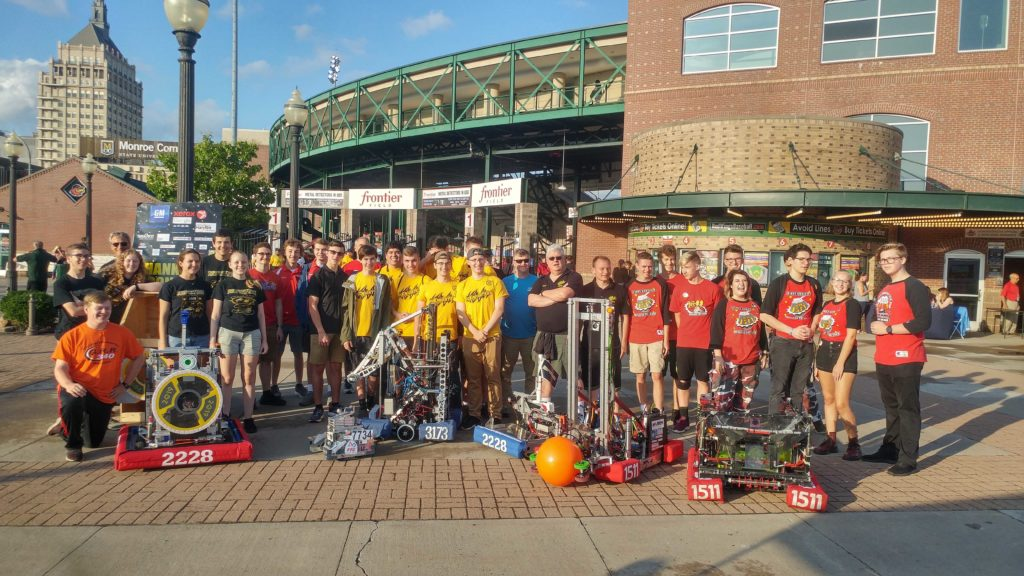 Photo of 4 robotics teams with their robots in from on Frontier Field Stadium in Rochester, NY