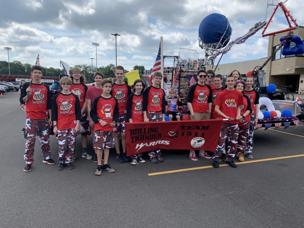 Team members dressed in red shirts and camo pants holding a Team 1511 banner in front of a parade float with robots on it
