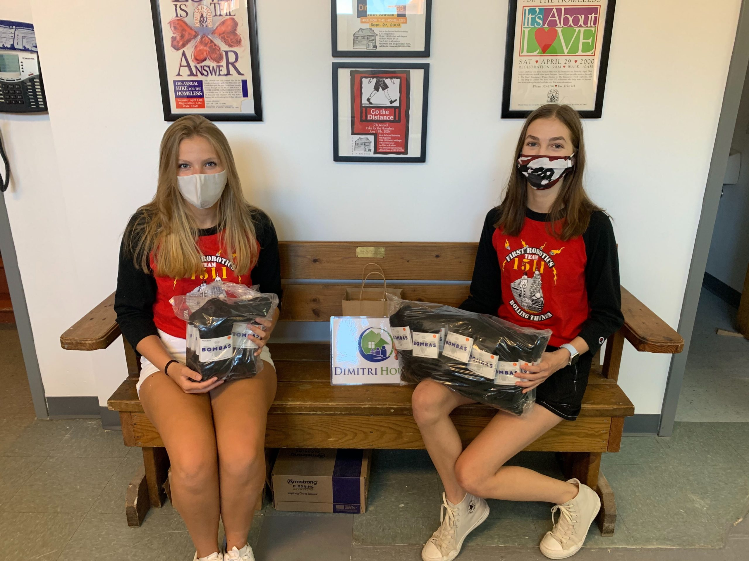 2 students hold packages of Boombas Socks donations at Dimitri House