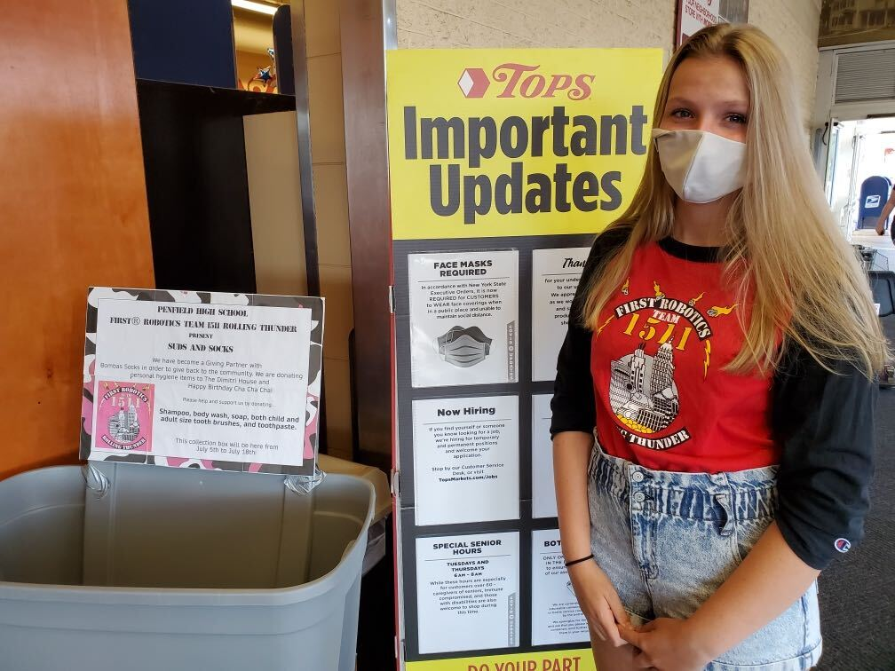Student in front of a donation collection bin at Tops Market