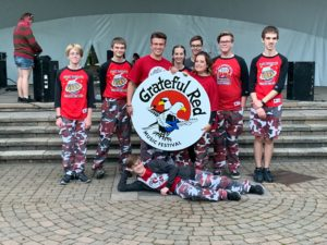 9 students in front of ampitheatre holding a round Grateful Red Musical Festival Sign