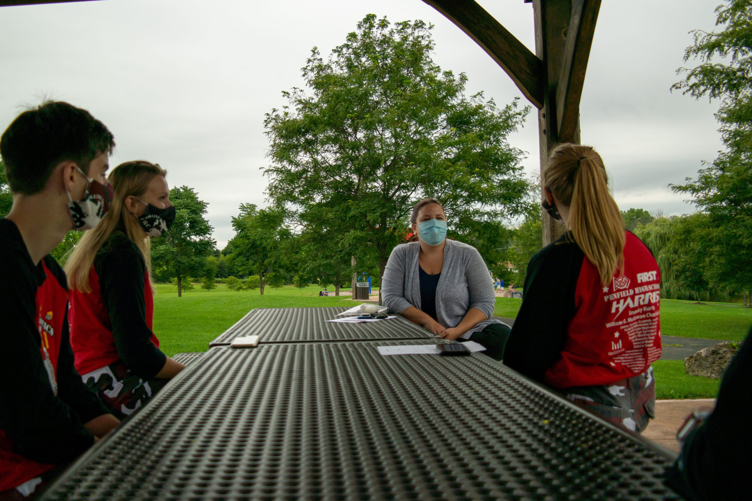 2 students sitting at a picnic table with Assmebly member Jen Lunsford