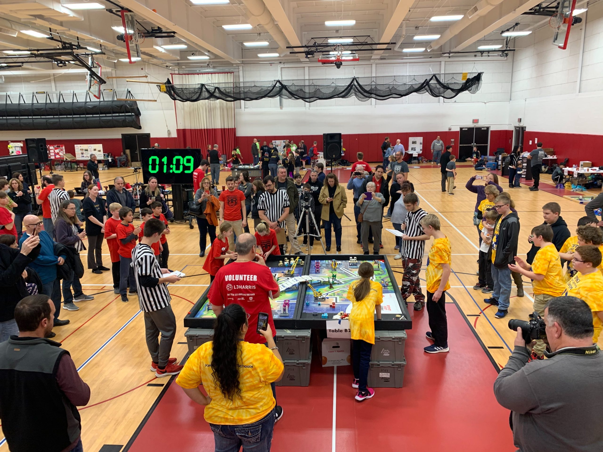 Photos of 2 FLL teams competing at a competition table at a Regional FLL Competition held at Penfield High School
