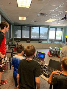 3 children standing behind laptops looking at a team robot