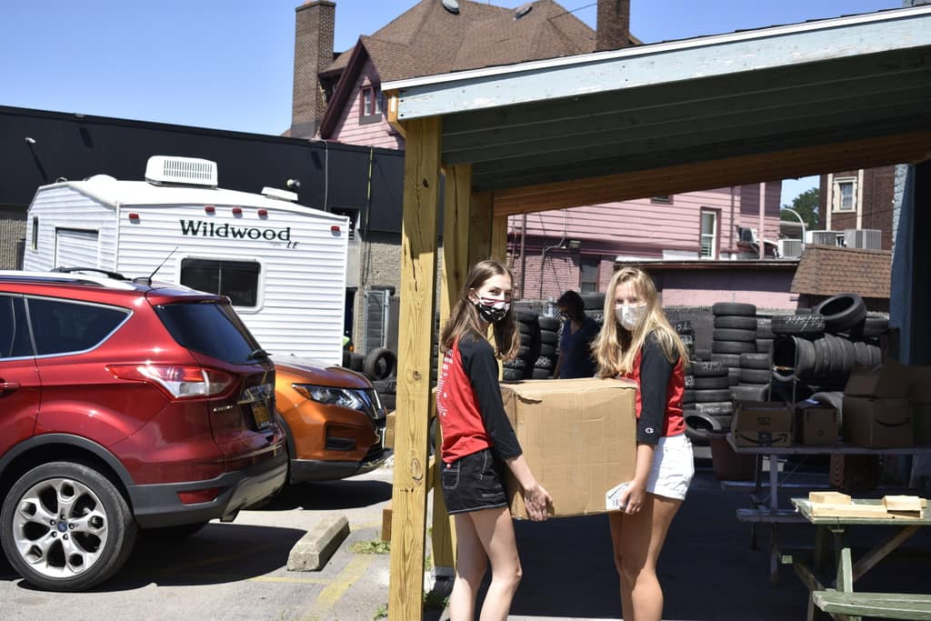 Photo of 2 students carrying a box of donations to Dimitri House