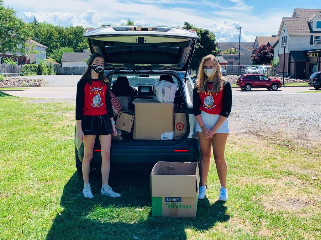 Photo of 2 students in front of car trunk full of Bombas Socks and personal care items for Dimitri House