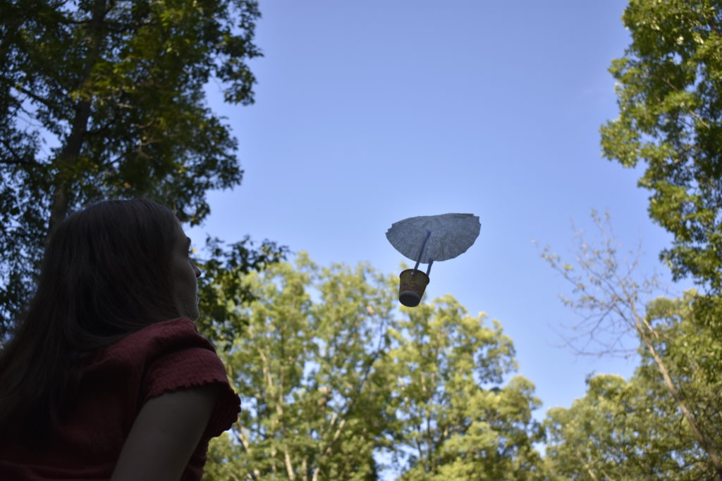 Photo of student looking up at homemade craft parachute