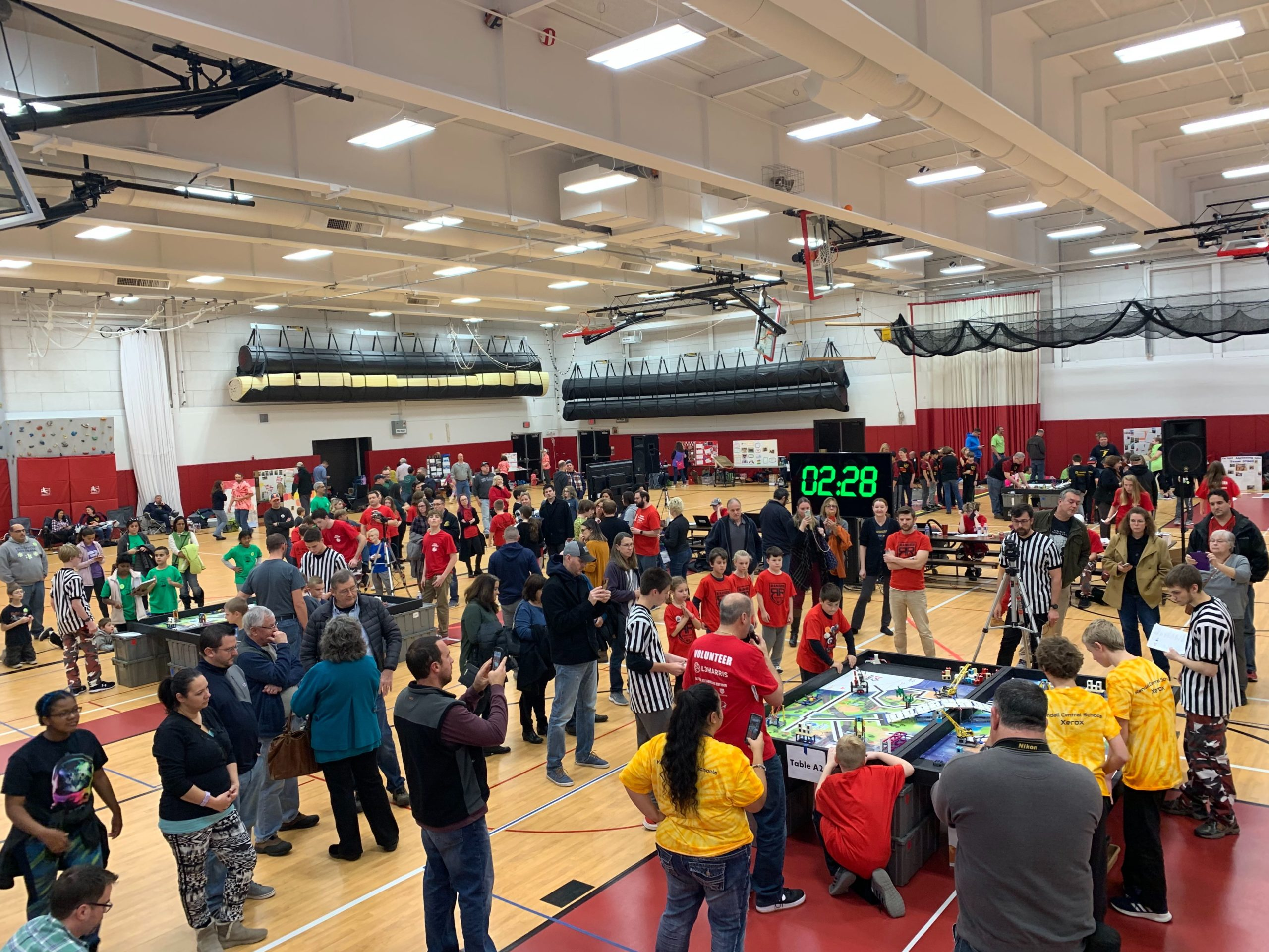 A gymnasium filled with FLL robotics teams, playing fields and spectators