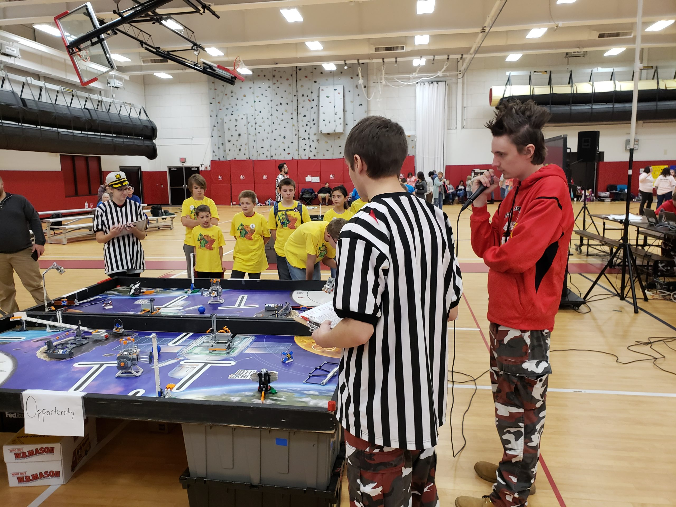 Photo of an announcer and a judge at a FLL Competition table