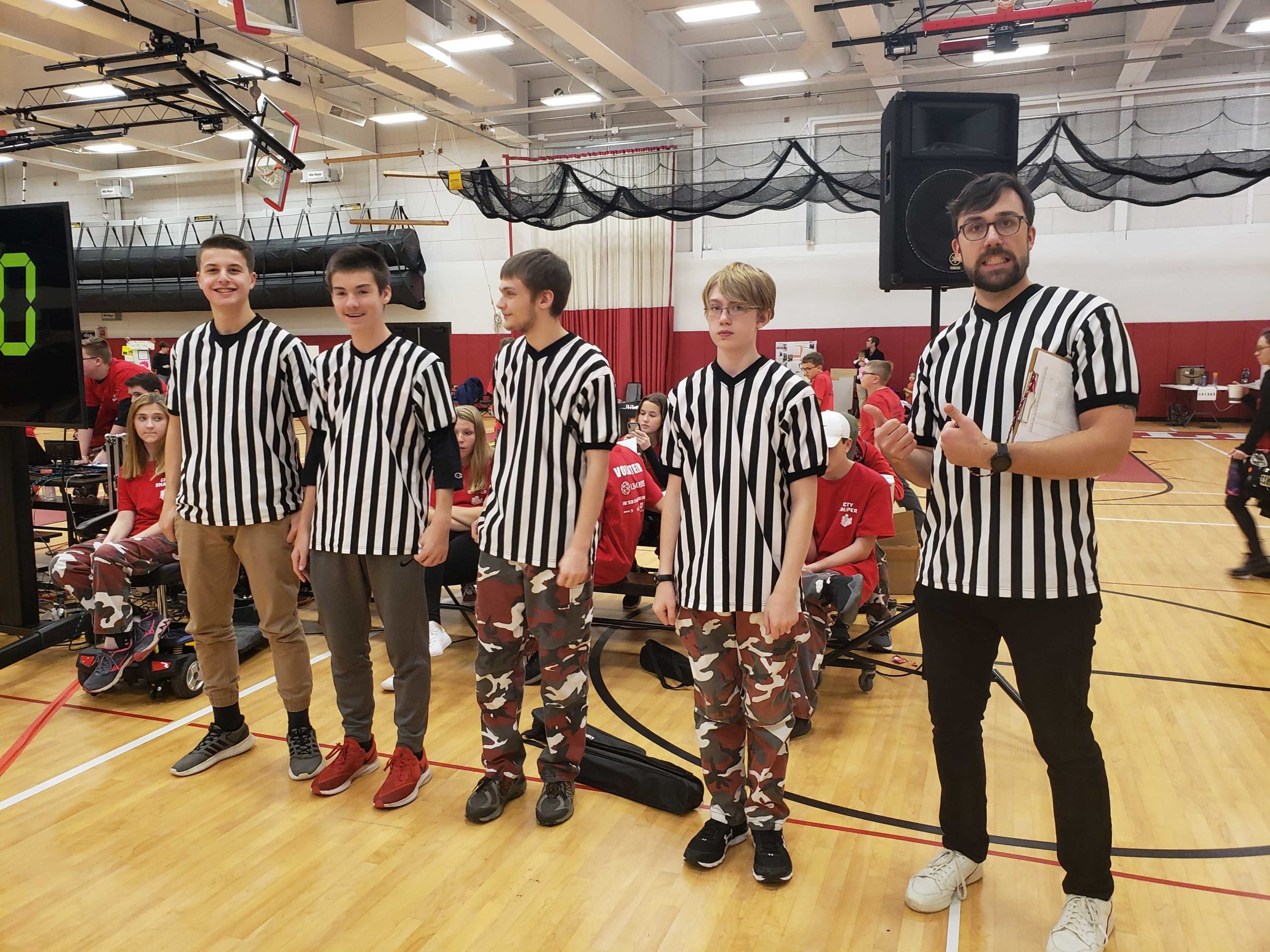 Photo of 5 referees in striped shirts at FLL Qualifier