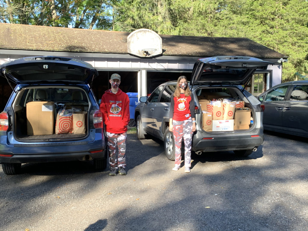 2 team members standing in front of 2 cars with trunks full of items for Happy Birthday Cha Cha Cha