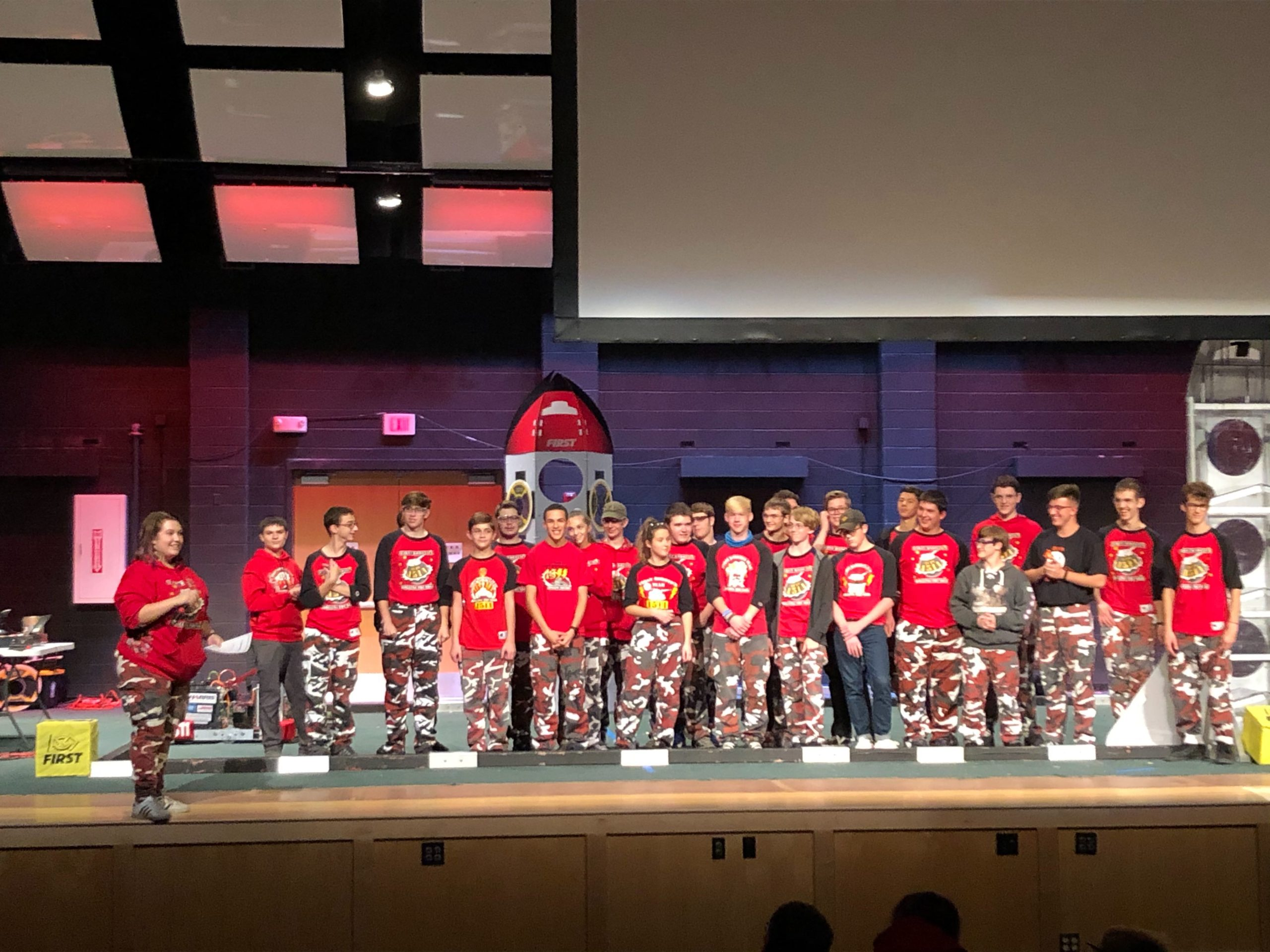FIRST Team 1511 students in red shirts and camo pants on an auditorium stage at Cage Match Event