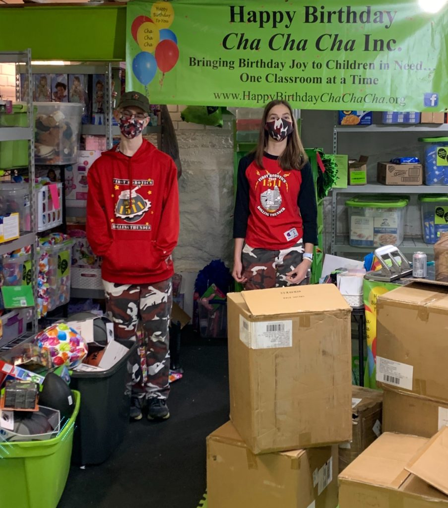 2 students standing in front of Happy Birthday Cha Cha Cha Sign with boxes of donations for Happy Birthday Cha Cha Cha