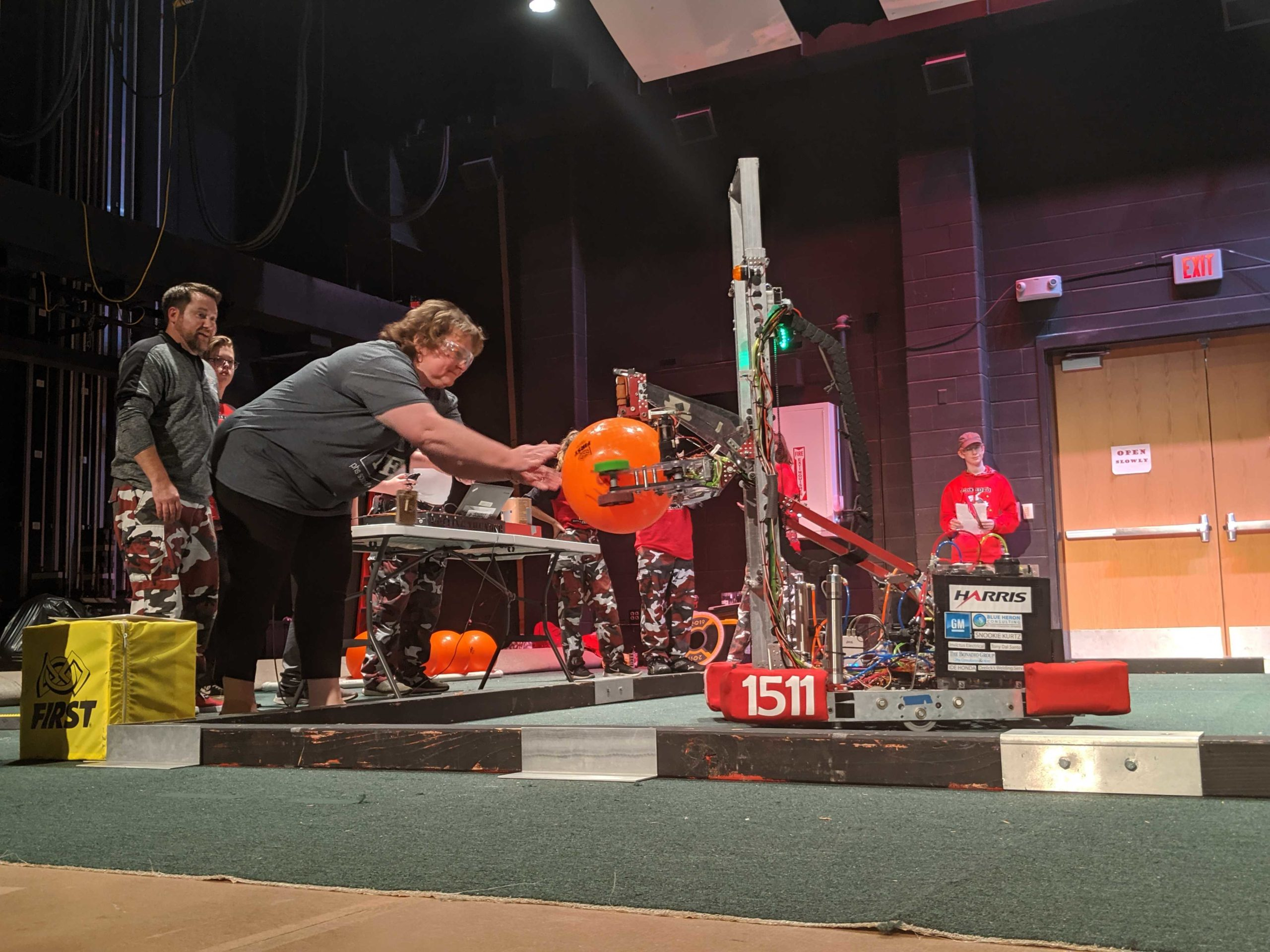 School administrator loading an orange ball into a robot at Cage Match Event