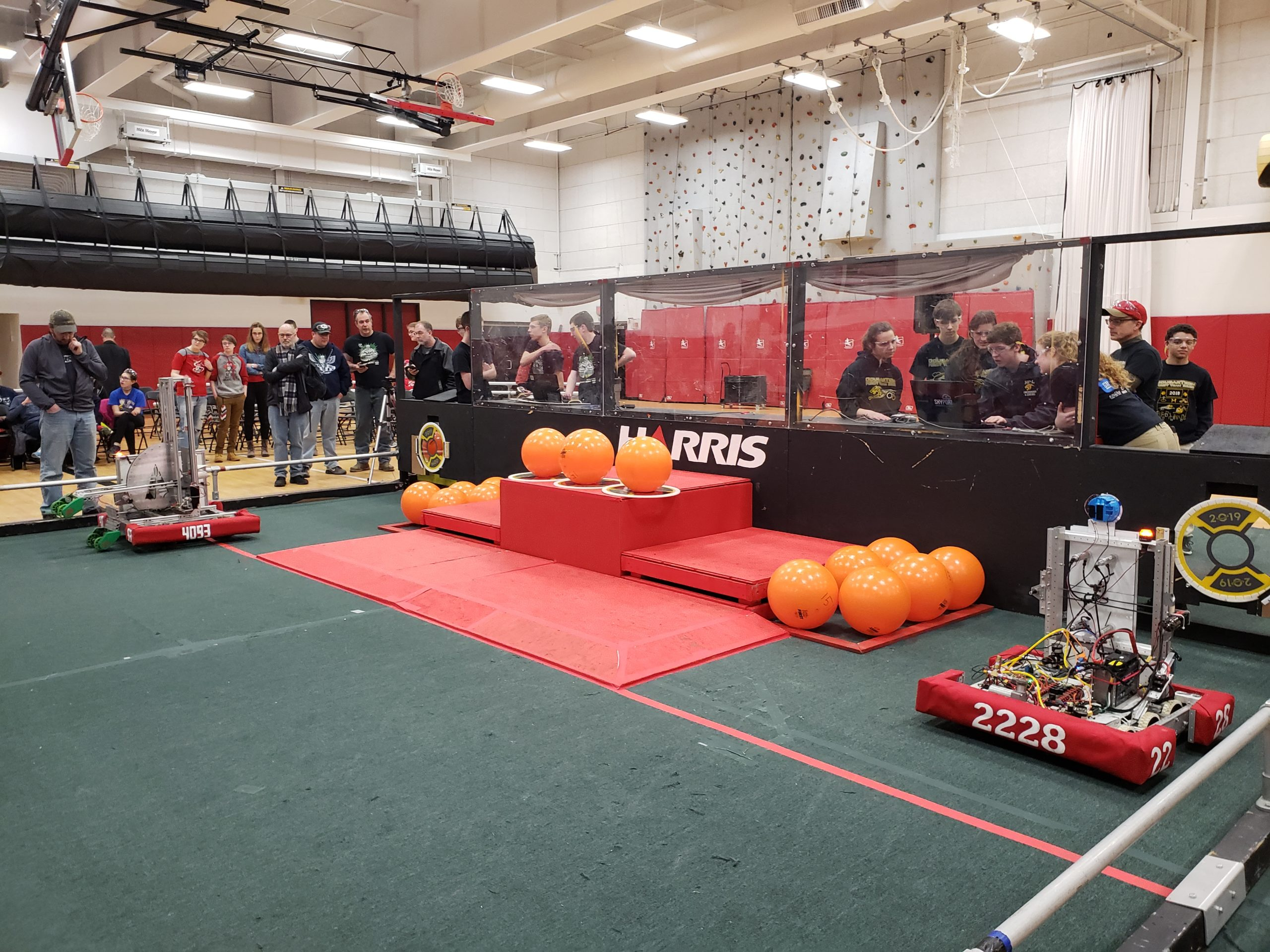 Photo of robotics field with 2 robots and many orange balls and spectators