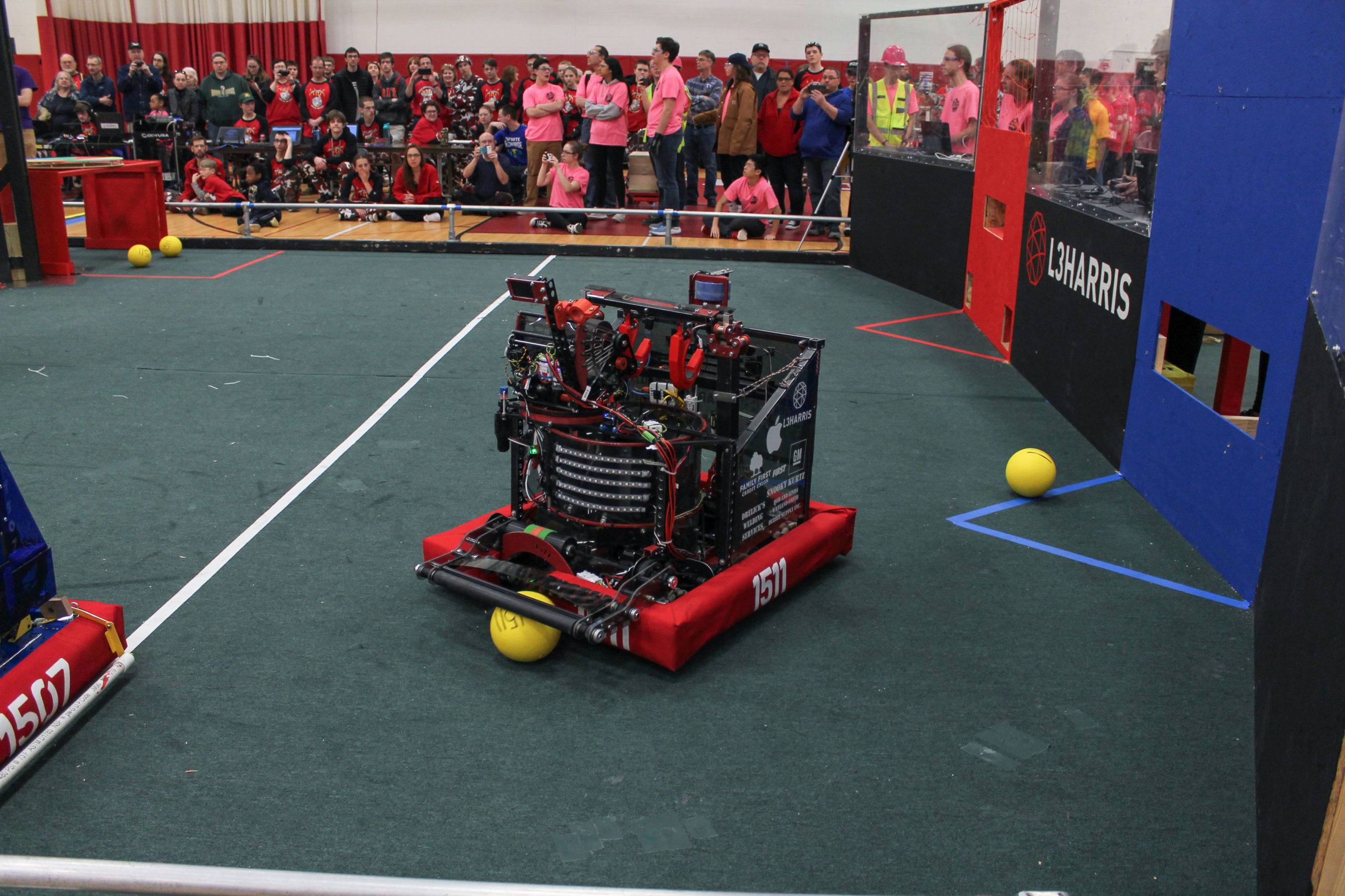 Photo of a robot running on a field with spectators watching at Rochester Rally