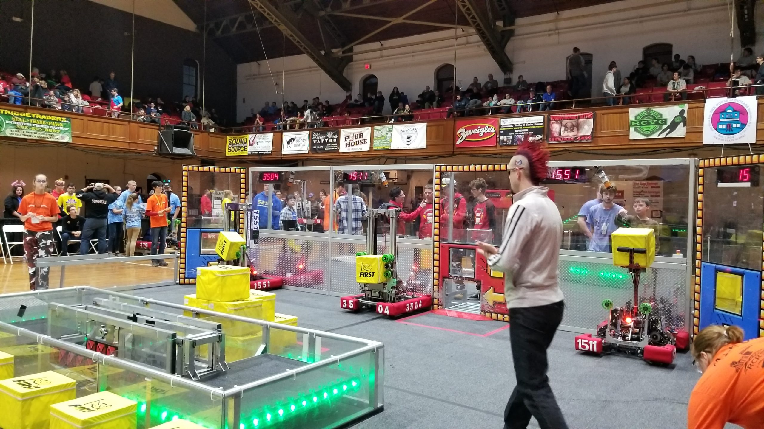 Photo of announcer on a playing field with robotics at Rochester Ruckus