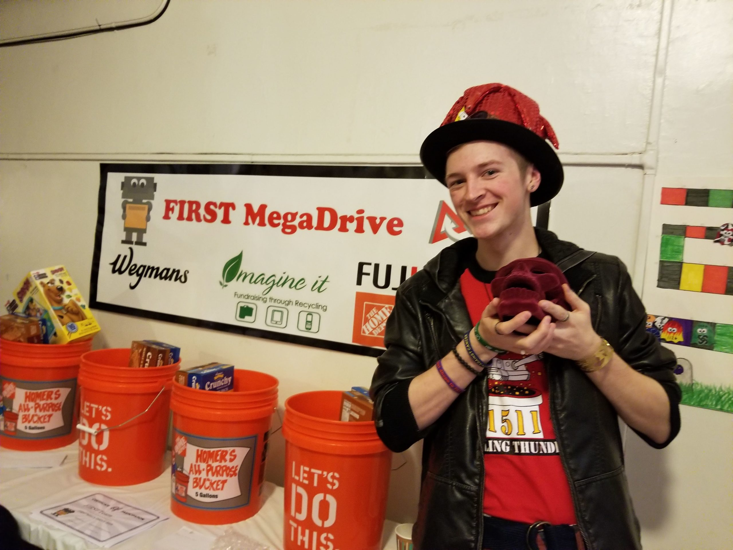 Photo of team member in front of Mega Drive sign with collection buckets at Rochester Ruckus