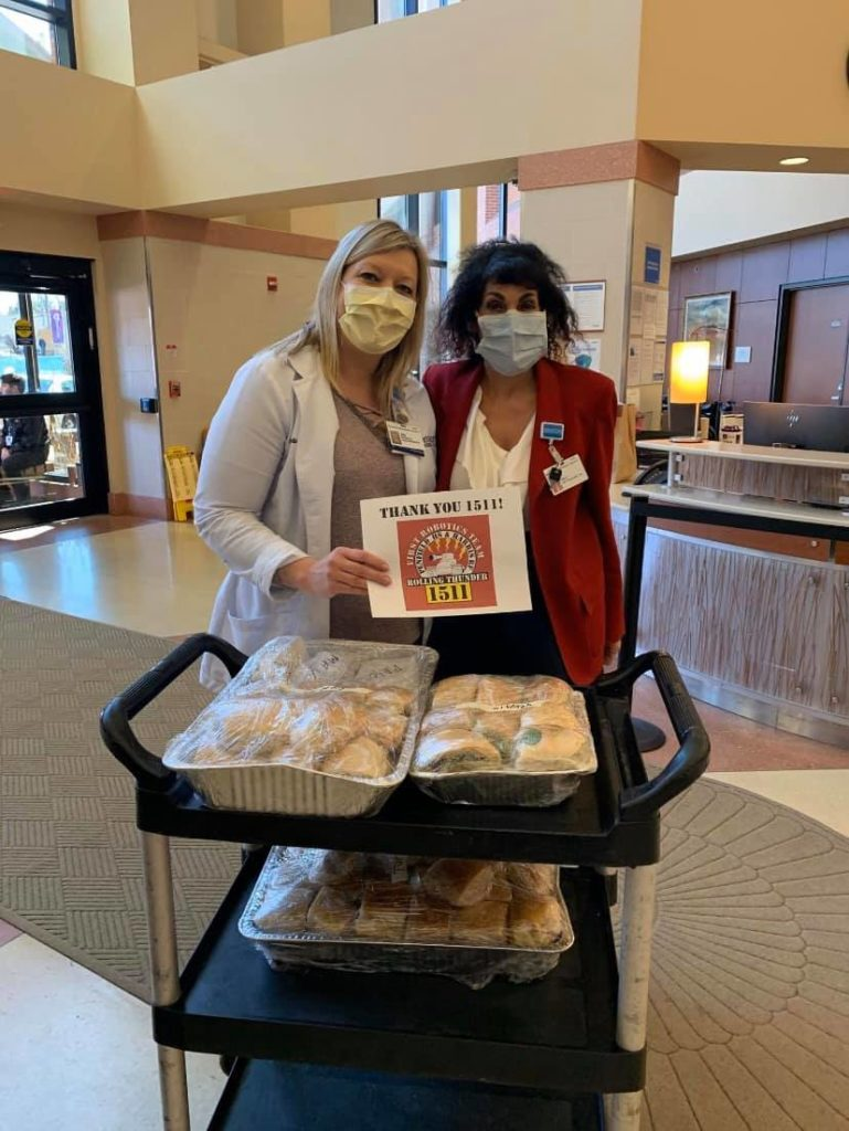Hospital workers in front of a cart of sandwiches donated by Team 1511