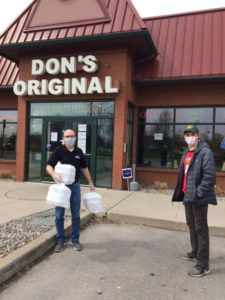 Student picking up food from Don's Original Restaurant for Health Care Workers