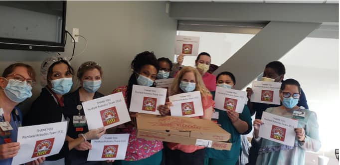 Healthcare workers holding Thank You 1511 Signs for pizza delivery