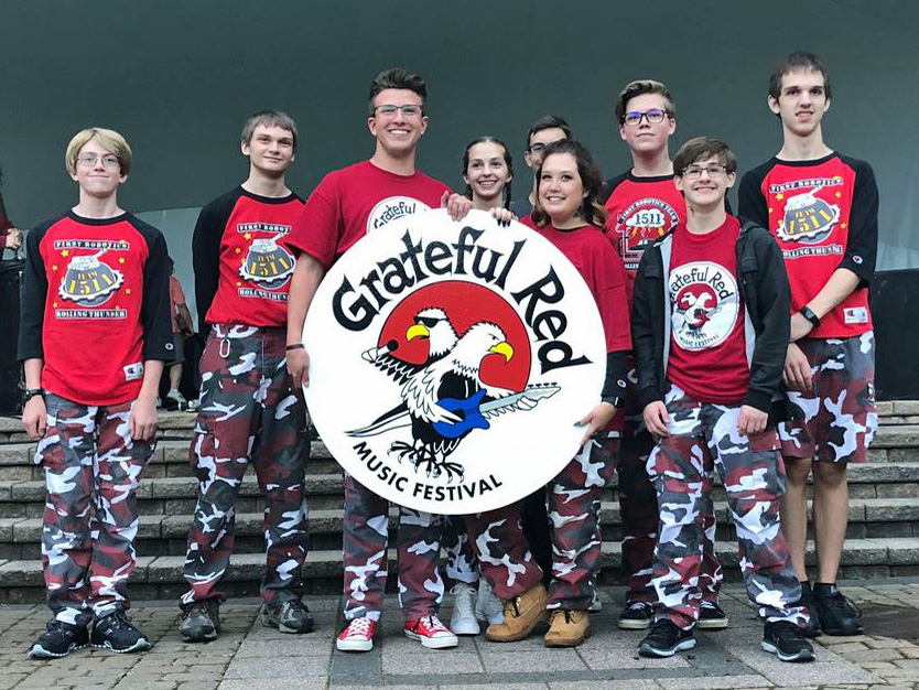 Team Members in uniform holding a Grateful Red Music Fest Sign