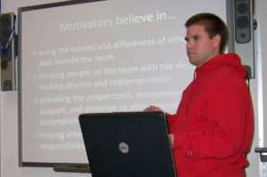 eam mentor presenting in front of screen that says motivators believe in...
