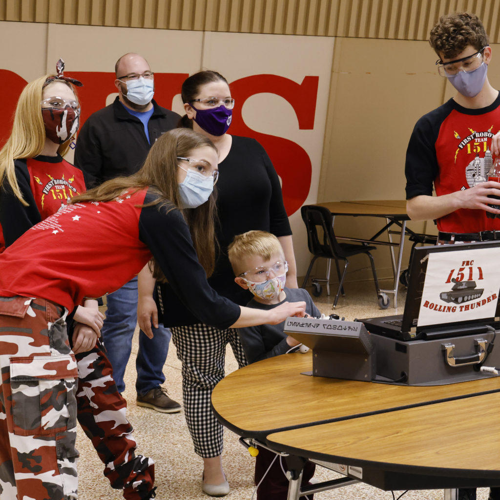 Team members showing a child how to work the robot controls