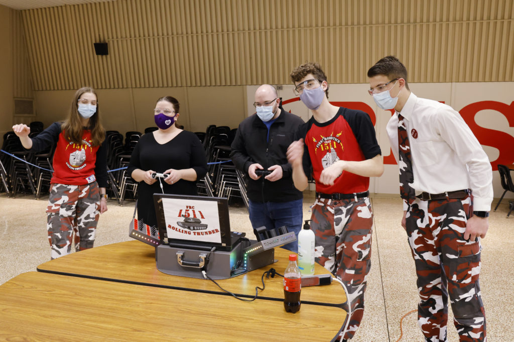 NYS Assemblymember Jen Lunsford and her husband driving a robot with team members coaching them