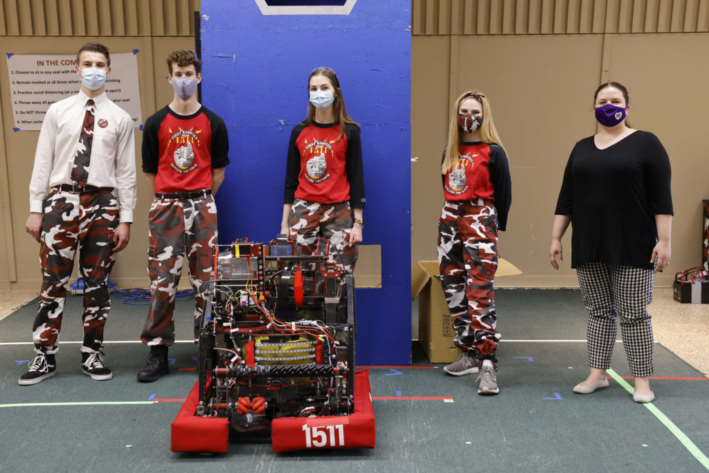 Team members standing behind a robot with NYS Assemblymember Jen Lunsford