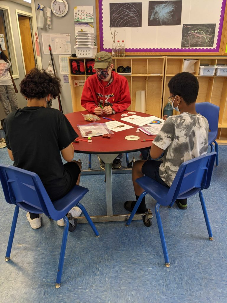 Team member sitting at a table teaching 2 youth a STEAM activity