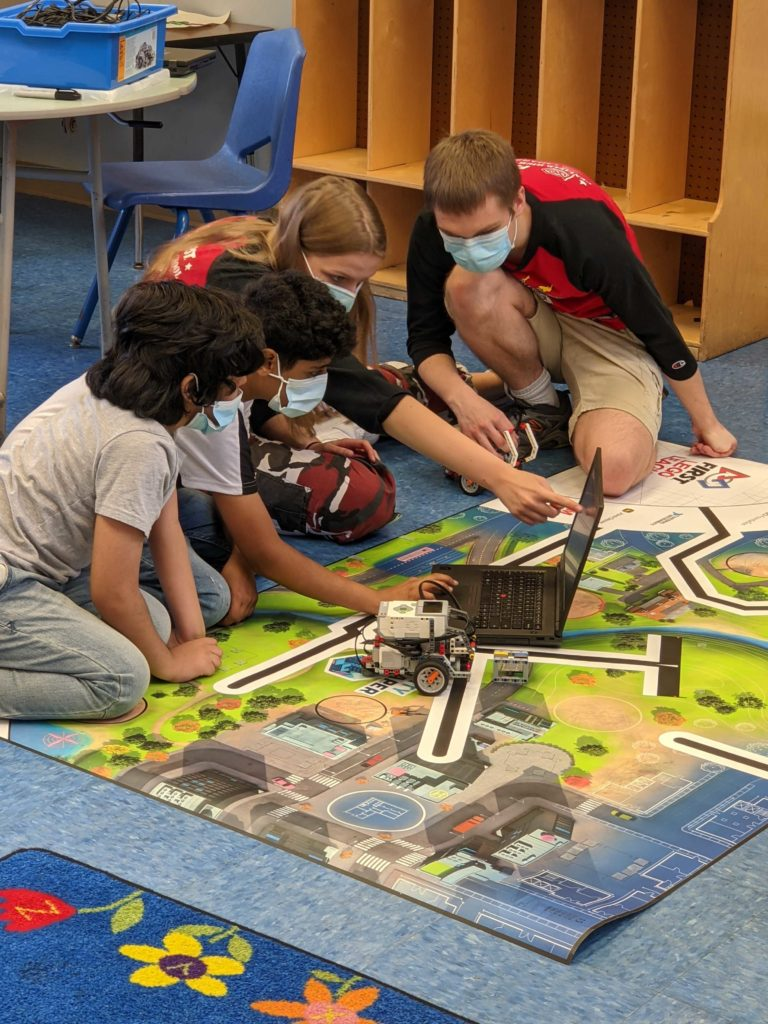 2 team members and 2 youth sitting by a game mat learning how to program an EV3 robot